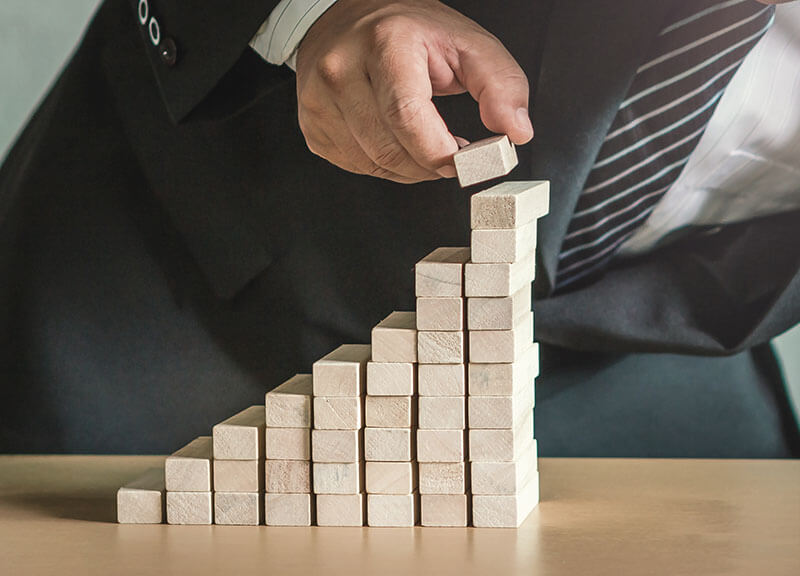 Asset management for foundations - businessman builds wooden blocks to rise stairs